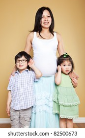 A shot of a pregnant Asian mother with her two kids