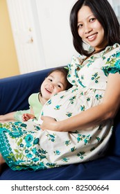A shot of a pregnant Asian woman sitting on the couch with her daughter