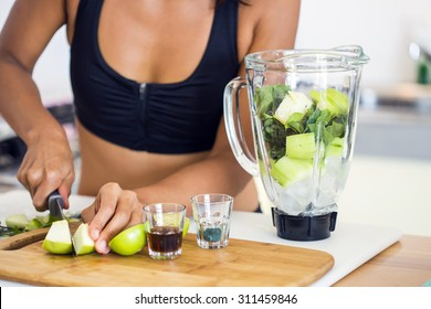 Shot of the preparation of a green detox juice. Hands of a woman cutting apple.