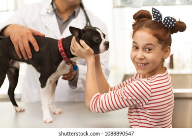 Shot of a pretty happy little girl smiling joyfully to the camera over her shouldern while petting her dog at the vet clinic. Cute girl bringing her puppy for veterinarian checkup