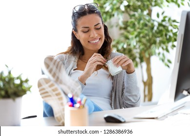 Shot of pretty young business woman eating yogurt while taking a break in the office.