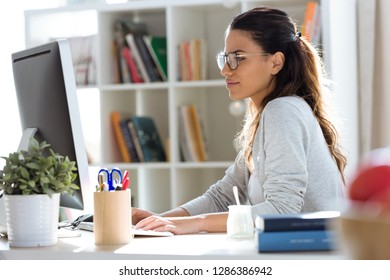 Shot of pretty young business woman working with her computer in the office.