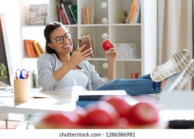 Shot of pretty young business woman using her mobile phone while eating red apple in the office.