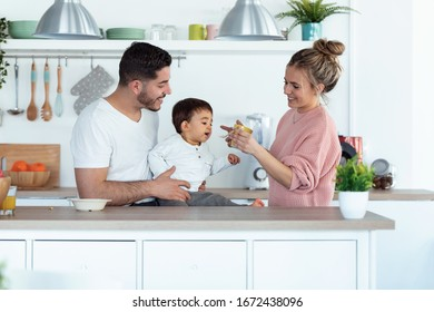 Shot of pretty young mother feeding her baby son while the father looking them in the kitchen at home.
