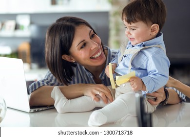 Shot of pretty young mother with her baby playing with notebook at home.