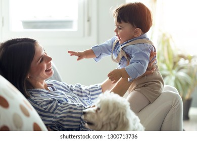 Shot of pretty young mother with her baby playing and loving in the living room at home.