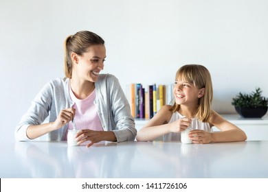 Shot of pretty young mother and her daughter looking to each other while eating yogurt at home.