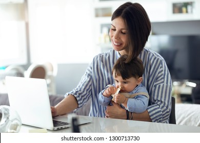 Shot of pretty young mother working with laptop while her baby sitting on her legs at home.