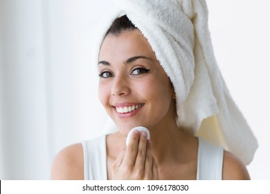 Shot of pretty young woman is cleaning her face while looking in the mirror in the bathroom.