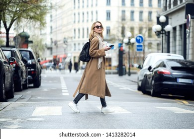 Shot of pretty young woman crossing the street while holding the smartphone and looking sideways.
