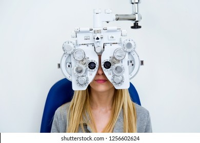 Shot of pretty young woman doing eyesight measurement with optical phoropter in ophthalmology clinic.