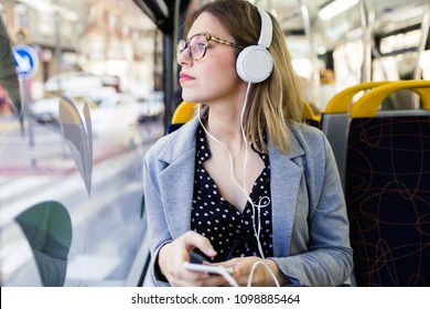 Shot of pretty young woman listening to music with mobile phone at the bus.
