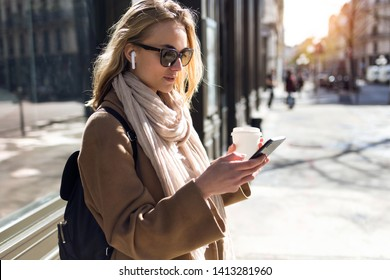 Shot of pretty young woman listening to music with wireless earphones and the smartphone in the street.