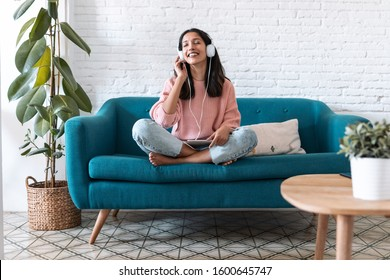 Shot of pretty young woman listening to music with digital tablet and relaxing while sitting on sofa at home.