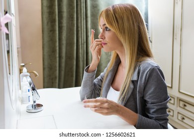 Shot of pretty young woman putting on contact lenses while sitting in front of the mirror at home.