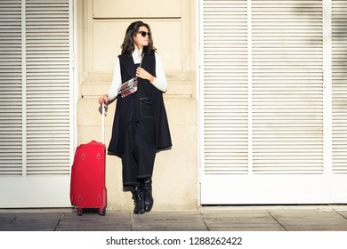 Shot of pretty young woman standing with suitcase while waiting her train in the street.