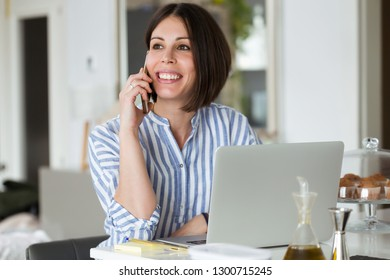 Shot of pretty young woman using her mobile phone while working with laptop at home.