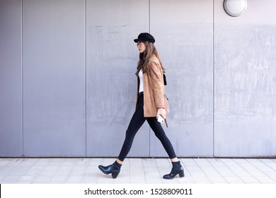 Shot of pretty young woman walking while holding her mobile phone in the street.