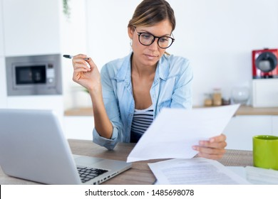 Shot of pretty young woman working with laptop and documents in the kitchen at home.