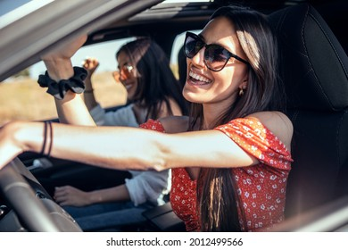 Shot of pretty young women singing while driving a car on road trip on beautiful summer day.