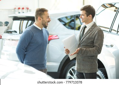 Shot of a professional car salesman and his male customer talking at the dealership salon. Mature man choosing a new automobile assistant manager helpful friendly advice occupation job