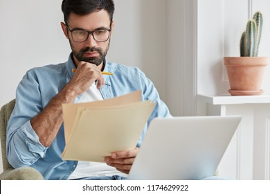 Shot of professional computer expert reads attentively instruction how use application, wears glasses, holds papers. Graphic designer creats logotyp for prosperous company uses modern netbook for work