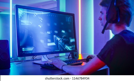 Shot of the Professional Gamer Playing in First-Person Shooter Online Video Game on His Personal Computer. Room Lit by Neon Lights in Retro Arcade Style. Online Cyber e-Sport Internet Championship.