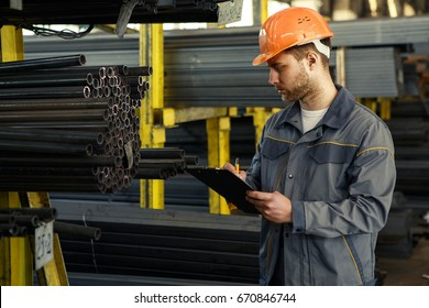 Shot of a professional metalworker wearing protective uniform and hardhat writing on his clipboard working at the metal factory copyspace engineering metalworking industry job controlling occupation