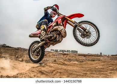 Shot of the professional motocross rider on his motorcycle on the extreme terrain track. Biker flying on a motocross motorcycle. Construction background and sky.