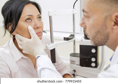 Shot of a professional ophthalmologist examining his Asian female patient while working at the clinic profession occupation emdicine healthcare ethnicity vision sight eyes lifestyle specialist