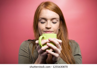 Shot of quiet beautiful woman smelling coffee over pink background.