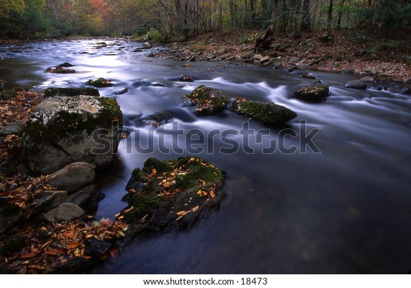 A shot of quiet stream meandering thru the mountain side taken with a slow shutter speed to emphasize the silkiness of the water as it flows over the rocks.