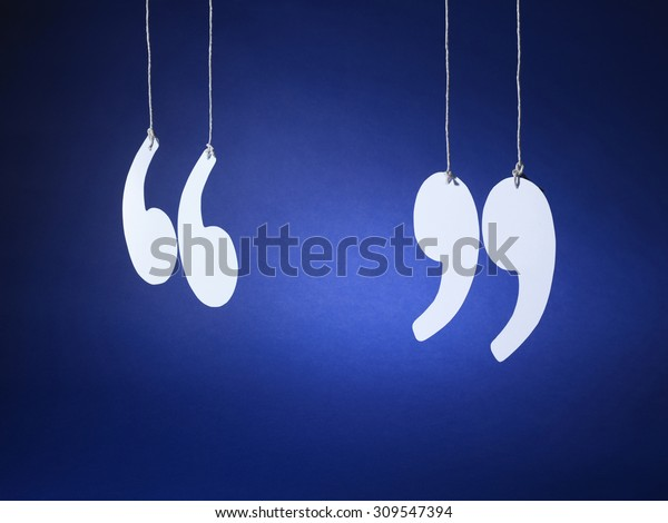 shot of quotation marks or inverted commas cut out from white card and suspended on string on a blue background.