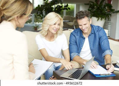 Shot of an real estate agent consulting with her client at home. Businesswoman presenting her idea to the middle aged couple while sitting at home.