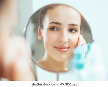 Shot of a reflection of a young woman applying the powder in the round mirror