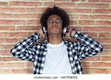 Shot of relaxed afro-american young man listening to music with headphones leaning on stone wall at home.