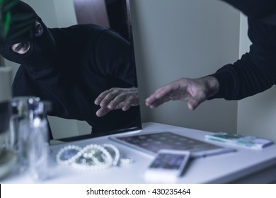 Shot of a robber stealing valuables from a table