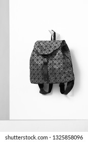 Shot of rucksack with fastex closure, adorned with gray geometric mosaic, hanged on a single wall-mounted coat rack. The accessory is isolated on the snowy background. Trendy women's fashion item.