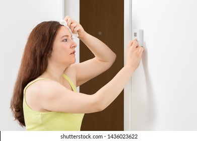 Shot of a sad woman sweating suffering a heat stroke and adjusting a digital thermostat in the office