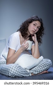 Shot of a sad young woman with a mug in her hand