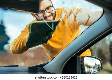 Shot of a satisfied man cleaning the windows on his car from outside.