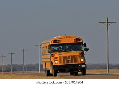 A shot of a School Bus that's on a High way that's with blue sky and north of Nickerson Kansas USA on 3-3-2018.