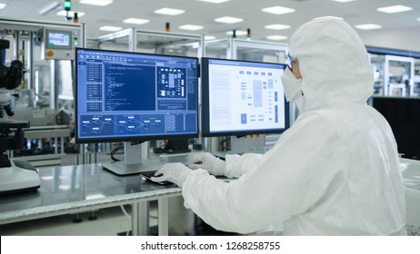Shot of a Scientists in Sterile Suits Working with Computers, Analyzing Data form Modern Industrial Machinery in the Laboratory. Product Manufacturing Process: Pharmaceutics, Semiconductors