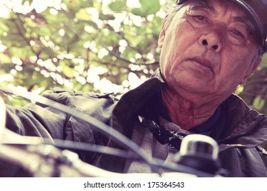 A shot of a senior asian man riding his bicycle