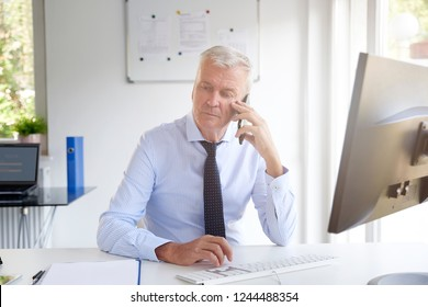 Shot of senior businessman using his cell phone and talking with somebody while sitting at office desk.