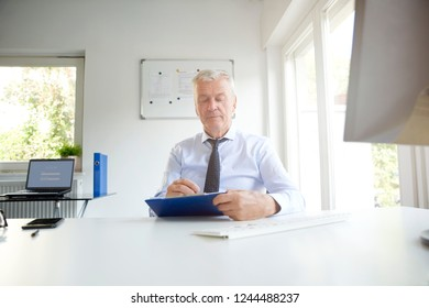 Shot of senior businessman wearing shirt and tie whil sitting in the office and doing some paperwork.