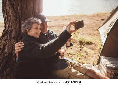 Shot of a senior couple taking a photo of themselves while outside a tent. Mature couple camping near a lake taking a selfie with mobile phone.