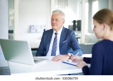 Shot of a senior executive financial businessman sitting in front of laptop and consulting with his young assistant in the office.