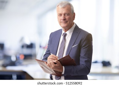 Shot of a senior financial manager writing notes into his diary while standing at office.