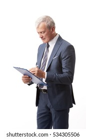 Shot of a senior professional man holding clipboard in his hand and doing some paperwork while standing at isolated white background.
